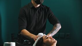 Man barber with tattoes drying out his client hair stock video