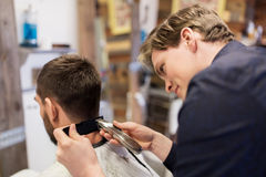 Man and barber with trimmer cutting hair at salon Royalty Free Stock Photos