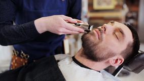 Man and barber with trimmer trimming beard at shop stock footage