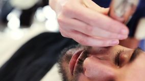 Man and barber with trimmer trimming beard at shop stock video