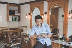 Man in barbershop with digital tablet Stock Photo