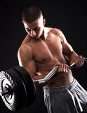 Man with bare chest performing barbell biceps curls Stock Photos