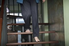 Man Descending Staircase. Man with bare feet descending a staircase, indoor shot Stock Image