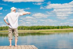 A man with bare feet is standing on a wooden pier and points to. The side in front of a beautiful lake Stock Images