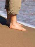 Man barefood on the beach. Male feet with rolled up pants on the shoreline Stock Image