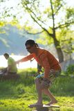Man barefoot is training on balance board on green meadow. Next to the river on sunny evening Royalty Free Stock Images