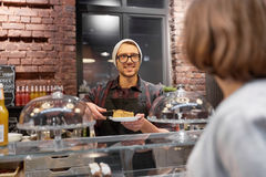 Man or barman with cake serving customer at cafe Royalty Free Stock Images