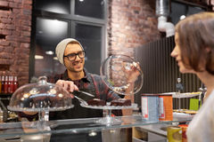 Man or barman with cakes serving customer at cafe Royalty Free Stock Photography