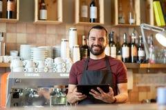 Man, bartender eller uppassare med minnestavlaPC på stången Arkivfoto