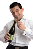 Man or bartender opening wine champagne. A cheerful bartender or man celebrating by opening a bottle of sparkling wine or champagne.  White background Royalty Free Stock Images