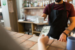 Man or bartender serving customer at coffee shop. Payment, people and service concept - man or bartender with cup serving customer paying money at coffee shop Stock Image