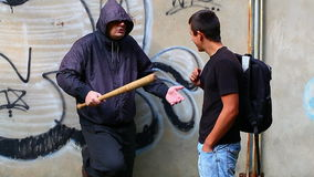 Man with a baseball bat against teenager stock video