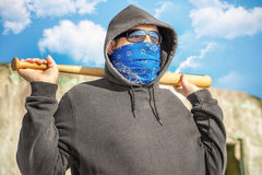 Man with a baseball bat on blue sky background Stock Images