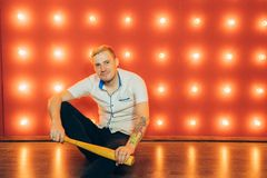 A man with a baseball bat in his hands posing on a red background of spotlights. stock photos
