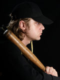 Man with baseball bat in profile. Man's profile portrait with baseball bat against a black background Royalty Free Stock Images