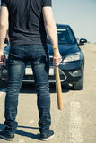 Man with baseball bat on the road Royalty Free Stock Image