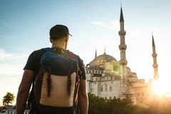 A man in a baseball cap with a backpack next to the blue mosque is a famous sight in Istanbul. Travel, tourism. A man in a baseball cap with a backpack next to royalty free stock images