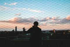 Man in Baseball Cap Standing Near Fence during Sunset Royalty Free Stock Photography