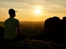 Man with baseball cap on top of mountain. Silhouette of rocks. Royalty Free Stock Photography