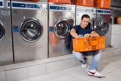 Man With Basket Of Clothes Sitting At Laundromat Royalty Free Stock Images
