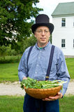 Man with a basket of greens. A man dressed in Nineteenth Century style holds a basket filled with mustard greens near a country road Royalty Free Stock Photo