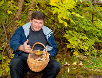Man with a basket of mushrooms on background of the autumn fores Stock Images
