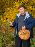 Man with a basket of mushrooms on background of the autumn fores Stock Photo