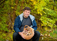 Man with a basket of mushrooms on background of the autumn fores Stock Photos