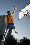 Man With Basketball Jumping Towards Hoop Stock Images