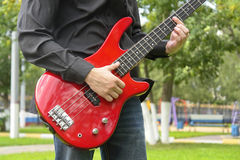 Man with bass guitar. Young man with bass guitar in the park stock images