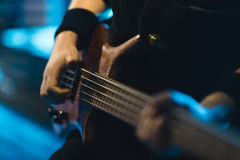 Man bass guitarist playing electrical guitar on concert stage Royalty Free Stock Photo