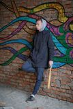 A man with a bat in his hands is standing on the background of graffiti royalty free stock photo