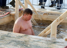Man bathes into cold water of ice-hole on Epiphany day. Russia Stock Photos
