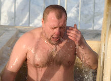Man bathes into cold water of ice-hole on Epiphany day. Russia Royalty Free Stock Photo
