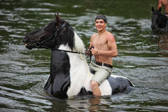 Man bathes horse in the river. Young man astride horse go down the river Stock Photo