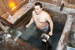 The man bathes in an ice-hole stock images