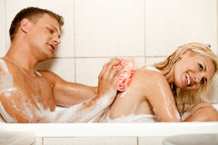 Man bathing his wife Stock Image