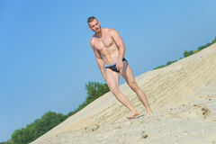 Man in a bathing suit on the beach stock photo