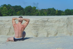 Man in a bathing suit sits high on a sand hill stock images