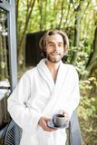 Man in bathrobe on the balcony in the forest. Portrait of a handsome man in bathrobe standing with coffee on the balcony in the beautiful forest royalty free stock images