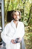 Man in bathrobe on the balcony in the forest. Portrait of a handsome man in bathrobe standing with coffee on the balcony in the beautiful forest stock image