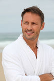 Man with bathrobe on the beach Stock Images