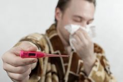 A man in a bathrobe blows his nose in a handkerchief and shows a thermometer. concept: illness, cold Stock Image