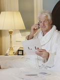 Man In Bathrobe With Cellphone And Document In Bed Royalty Free Stock Image