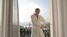A man in a Bathrobe dancing on the terrace, slow motion. 4K stock footage