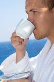 Man in bathrobe drinking coffee on balcony Stock Photos