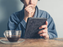 Man in bathrobe having coffee and using tablet Stock Photo