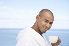 Man In Bathrobe Holding Coffee Cup Outdoors Royalty Free Stock Image