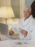 Man In Bathrobe With Laptop And Document In Bed Royalty Free Stock Photos