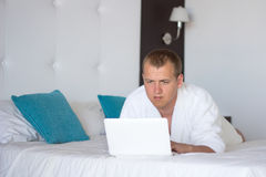 Man in bathrobe with laptop in hotel room Royalty Free Stock Image